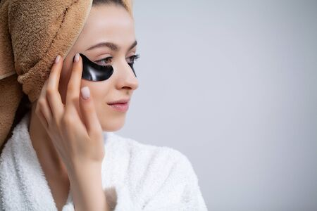 Beautiful woman in a white coat applies patches to the eyes for skin care Standard-Bild