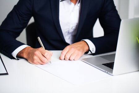 Businessman sitting at office desk signing contract