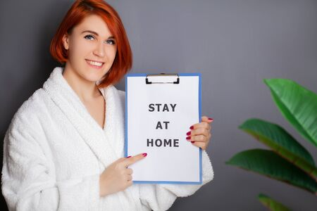 Woman holding blank with inscription stay at home calling for stop spreading covid-19