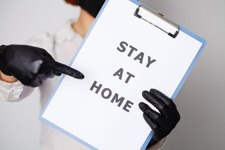 Woman holding blank with inscription stay at home calling for stop spreading covid-19. Stock Photo