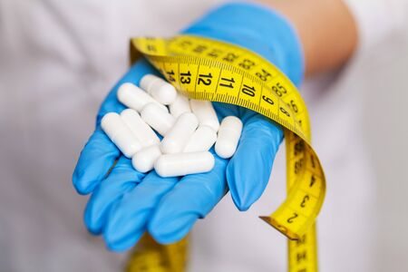 Female doctor in a white coat holding white pills for weight loss Фото со стока