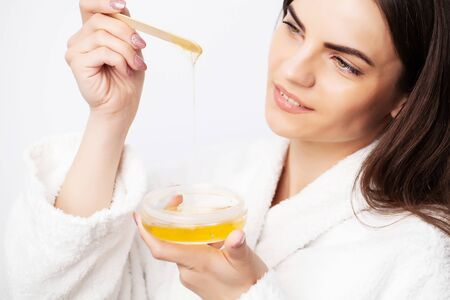 Care concept, woman holding bowl with wax for hair removal