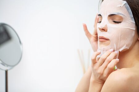 A woman uses a moisturizing mask to take care of her skin