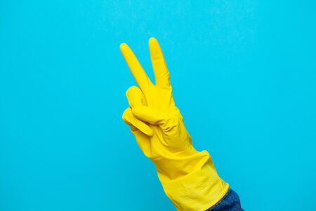 Hand in a yellow glove for cleaning.
