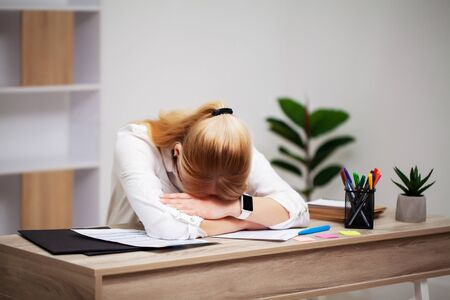 Tired young businesswoman exhausted at workplace in her office Stock Photo
