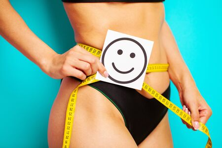 Slimming concept, slender woman measures the size of her waist with a measuring tape.