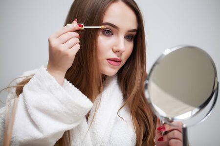 Beauty makeup, young woman with beautiful skin holding eyelash brush near eyes