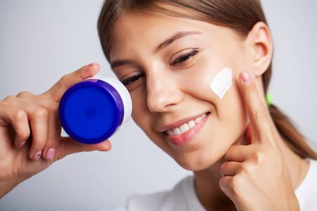 Skin care, young woman with beauty face use facial skin cream Archivio Fotografico