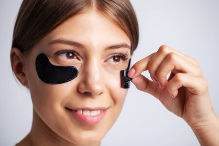 Beauty care, young beautiful woman with black patches for skin care under the eyes Standard-Bild