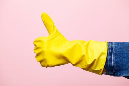 Close up hand in yellow glove for cleaning.