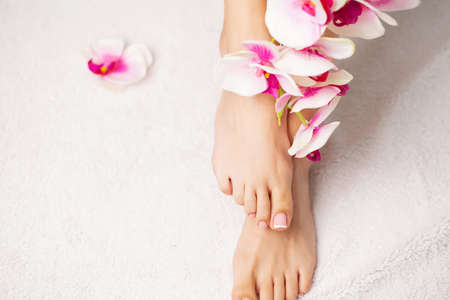 Long legs of a woman with a fresh manicure and orchid flowers 写真素材
