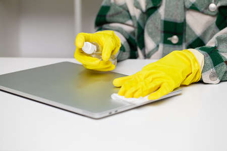 Woman wipes laptop from dust in the office at the table
