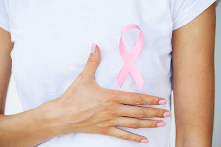 Close up of woman showing pink ribbon symbolizing breast cancer