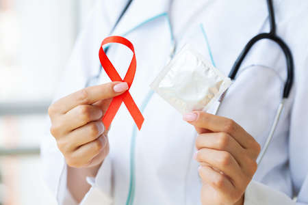 Doctor holding a red ribbon and condom calling for safe sex and protection from AIDS