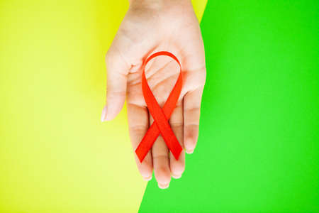 Close up of womans hands holding red ribbon calling for safe sex and behind