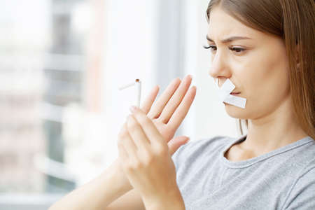 Stop smoking, a woman with a sealed mouth holding a broken cigarette