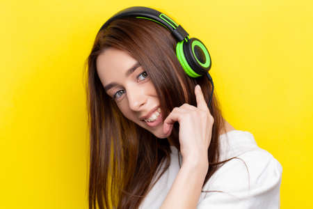 Beautiful young sexy girl DJ listening music in green headphones on a yellow background 写真素材