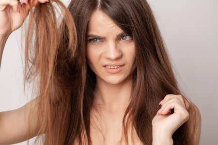 Very upset young woman has a problem with hair loss Archivio Fotografico