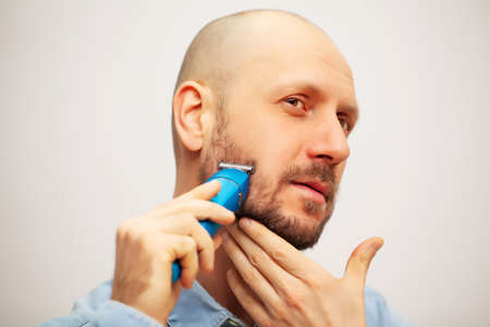 Handsome young bearded man trimming his beard with trimmer