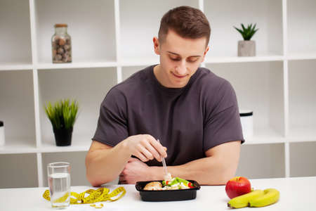 Shaped and healthy man holding a fresh meal bowl with meat Banque d'images