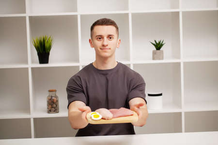 Shaped and healthy man holding a fresh meal board with meat Banque d'images