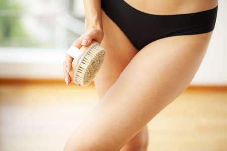 Woman arm holding dry brush to top of her leg, cellulite treatment and dry brushing. Reklamní fotografie
