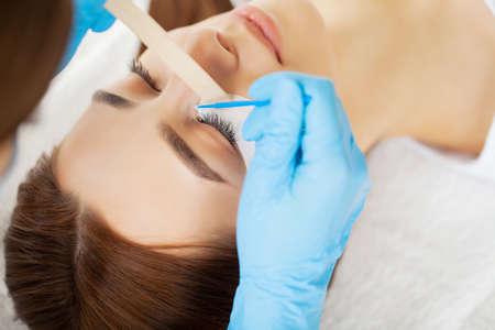 Eyelash extension procedure, professional stylist lengthening female lashes. Stockfoto