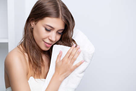 Young pretty woman wipes her head with a towel after taking a shower