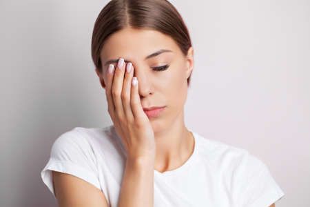 A young woman feels severe pain on her face touching the pain area with her hand