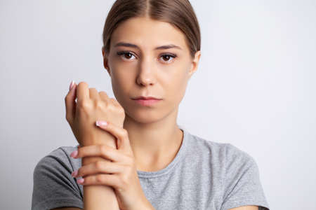 Young woman feels severe pain in her hand