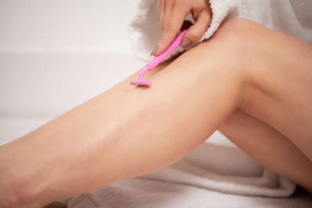 Woman using razor on her beautiful legs Archivio Fotografico - 154927805