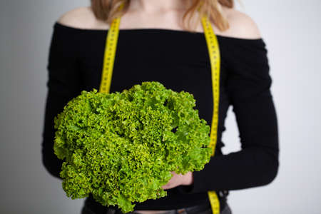 Closeup of woman holding broccoli with string tape to measure Archivio Fotografico - 154927486