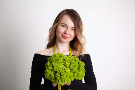 Closeup of woman holding broccoli with string tape to measure