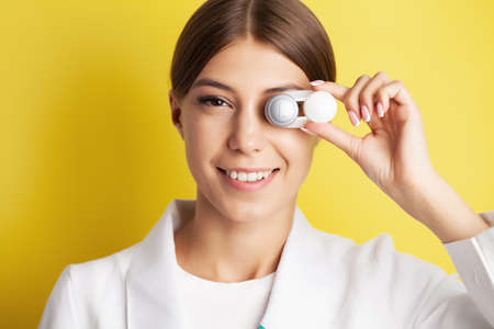 Close up of woman holding container with contact lenses