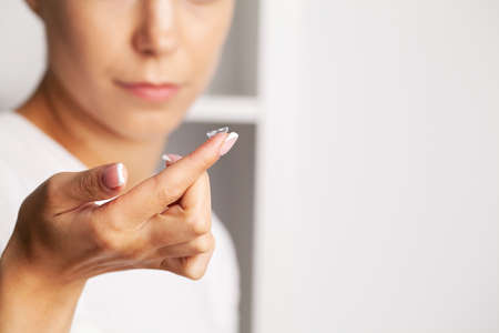 Close up of woman holding contact lens on finger Archivio Fotografico