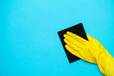 Close up of a woman in yellow mittens holding a cleaning rag