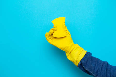 Close up of a woman in yellow mittens holding a cleaning rag Archivio Fotografico - 154933154