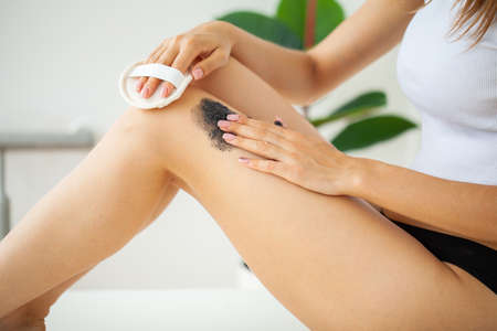Skin care, woman applies black scrub with sea salt Archivio Fotografico - 154934043