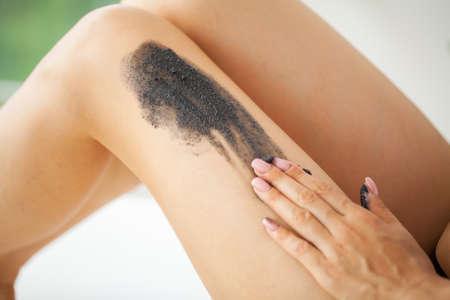 Skin care, woman applies black scrub with sea salt