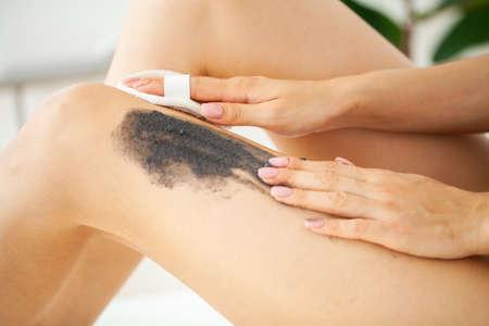 Skin care, woman applies black scrub with sea salt Archivio Fotografico - 154933298