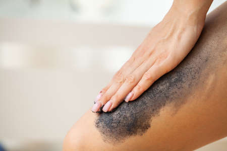 Skin care, woman applies black scrub with sea salt Archivio Fotografico - 154933775