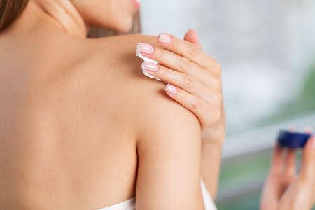 Skin care, woman wears moisturizer on skin