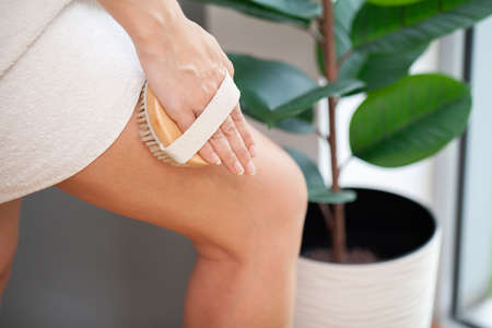 Cellulite treatment, woman arm holding dry brush to top of her leg. Archivio Fotografico - 154933114