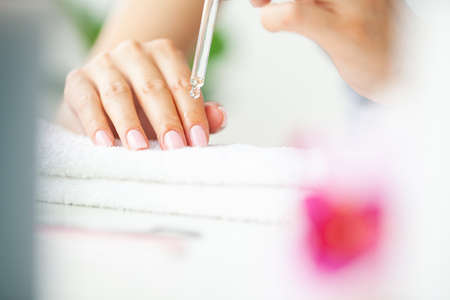 Moisturizing oil for cuticles, woman cares for hands and nails.