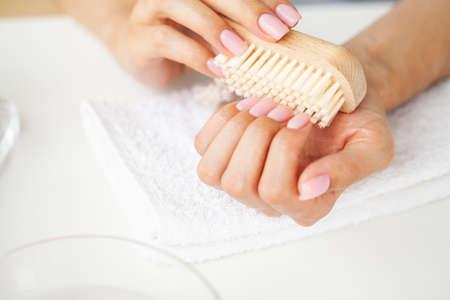Close up of woman using nail brush on fingernails Archivio Fotografico - 154932976