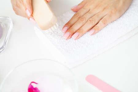 Close up of woman using nail brush on fingernails