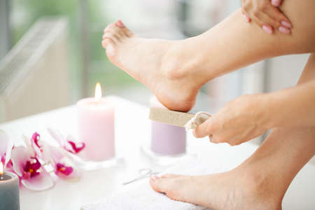 Woman cleans the heel of the foot with pumice Archivio Fotografico - 154933729