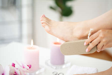 Woman cleans the heel of the foot with pumice Archivio Fotografico - 154933443