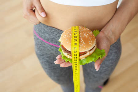 Diet concept, woman holding harmful fat burger with yellow measuring tape
