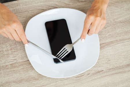 Dependence on the phone, close up a womans hands holding a fork and a knife over the phone on plate